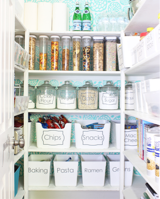 Tidy pantry, all food in jars or clear containers with labels. On white shelves with a pale green background
